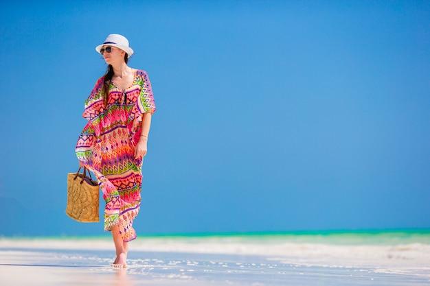 熱帯のビーチでの休暇中に帽子の若い女性