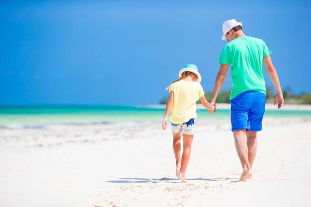 熱帯のビーチでの休暇中に小さな女の子とパパ
