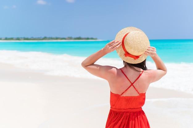 熱帯のビーチでの休暇中に帽子の若い女性。ビューティドゥル少女屋外の背面図