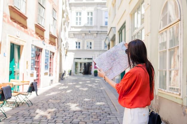 市内の市内地図を持つ若い女性