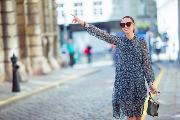 街を歩いている女性。ヨーロッパの都市で屋外の若い魅力的な観光客