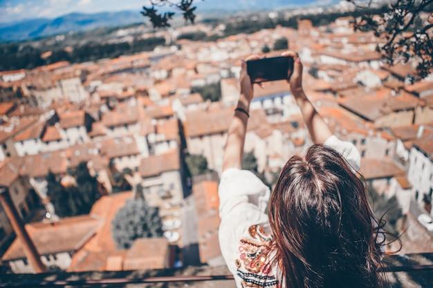 Молодая кавказская женщина делая фото мобильным телефоном от места наблюдения