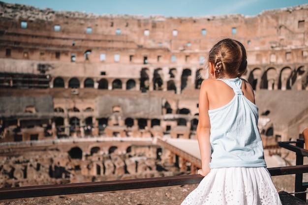 コロシアムの背景の上のローマで幸せな幼児の女の子