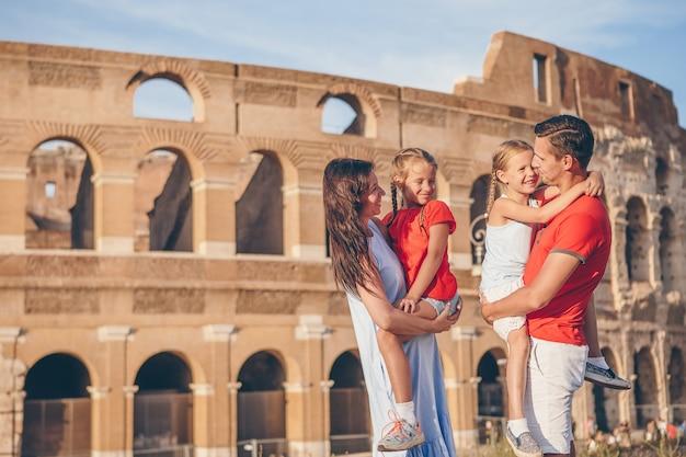コロシアムの背景の上のローマの幸せな家族。