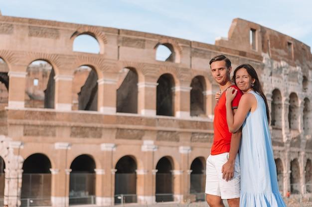 Счастливая пара в риме на фоне колизея. итальянские европейские каникулы