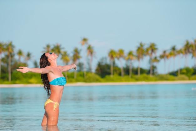 白い砂の熱帯のビーチでリラックスした美しい女性