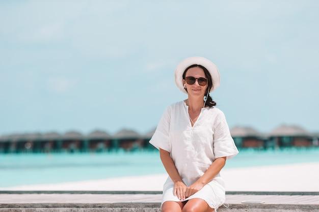 エキゾチックなリゾートのスイミングプールでリラックスした黄色の帽子を持つ女性