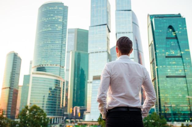 ガラスの超高層ビルに対して立っている間コピースペースを探している実業家の背面図