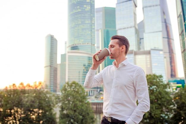 ガラスの超高層ビルに対して立ちながらコピースペースを探しているビジネスマン