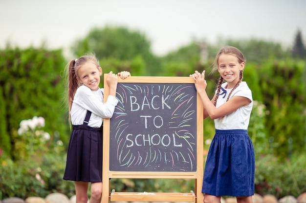 屋外の黒板と幸せな小さな女子学生