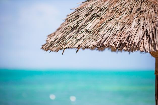 Крупным планом соломенный пляжный зонтик на тропиках