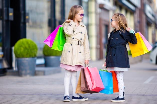 ショッピングでのかわいい女の子。買い物袋を持つ子供の肖像画。