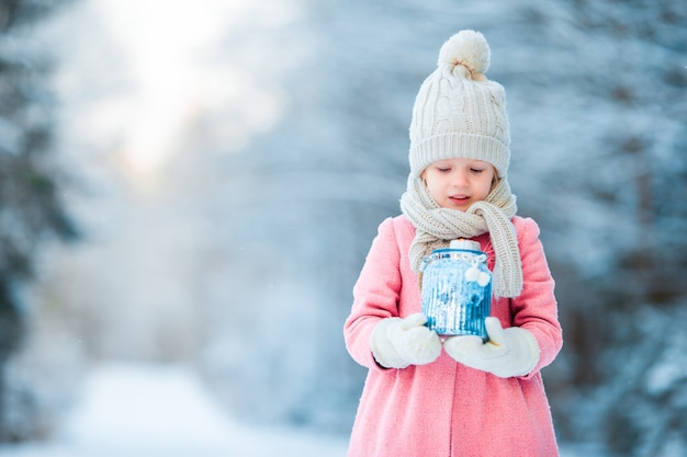 冬の日にクリスマスに凍った森の懐中電灯で愛らしい少女