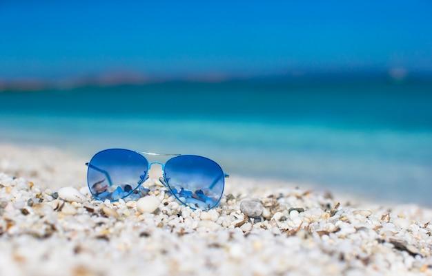 熱帯のビーチにカラフルな青いサングラスのクローズアップ