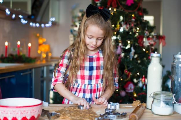 家庭の台所でクリスマスのジンジャーブレッドクッキーを焼く少女