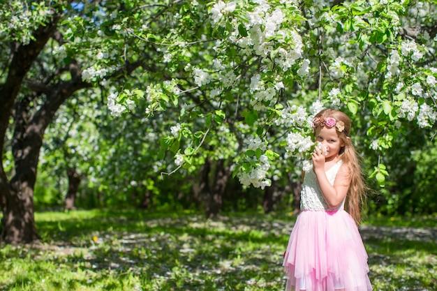 晴れた日に開花のリンゴ園でのかわいい女の子