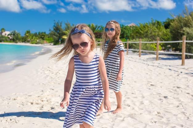 小さなかわいい女の子がビーチで楽しい時を過す