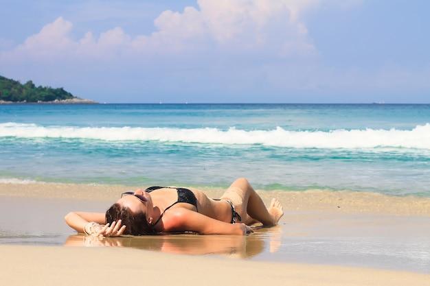 熱帯の白いビーチで夏休みを楽しんでいる若い女性