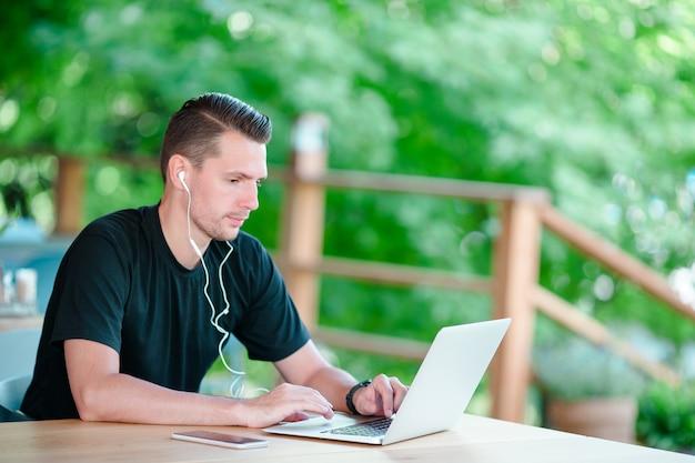 コーヒーを飲みながらの屋外カフェでラップトップを持つ若者。モバイルのスマートフォンを使用している人。