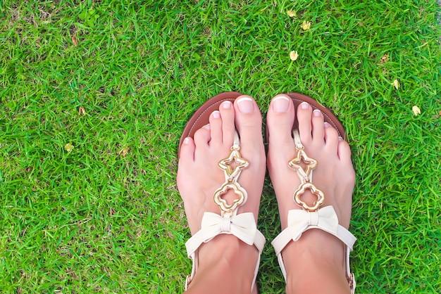 明るいフリップフロップと緑の草の上の足のクローズアップ