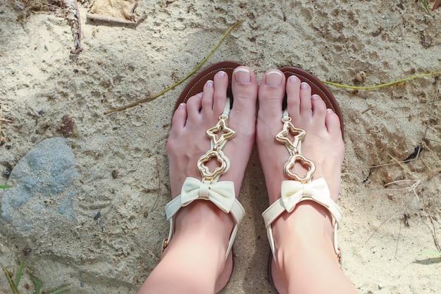 明るいサンダルと白い砂の上の足のクローズアップ