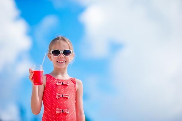 熱帯のビーチでカクテルを飲むかわいい女の子