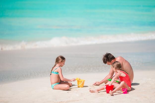 父とビーチ夏の熱帯の休暇を楽しんでいる小さな子供たち。