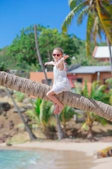 白いビーチで夏休みの間にヤシの木に座っているかわいい女の子