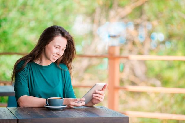 Молодая женщина с умным телефоном, сидя в одиночестве в кафе в свободное время