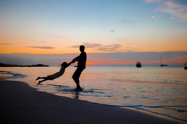 ビーチで夕日に小さな女の子と幸せな父のシルエット