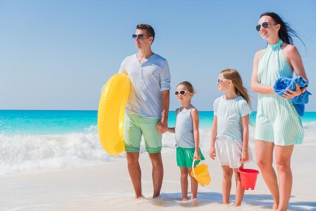 泳ぐつもりの熱帯のビーチでの休暇に幸せな美しい家族