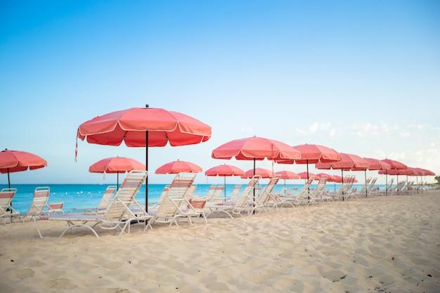 Райский вид на тропический пустой песчаный пляж с зонтиком и шезлонгом