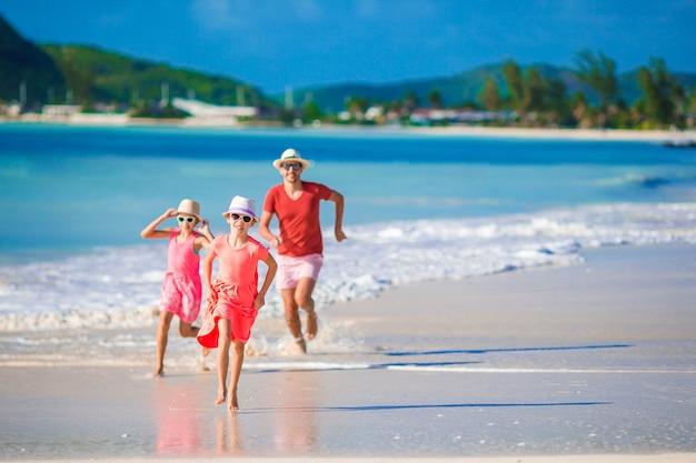 夏のビーチでの休暇中に楽しんで幸せな家族