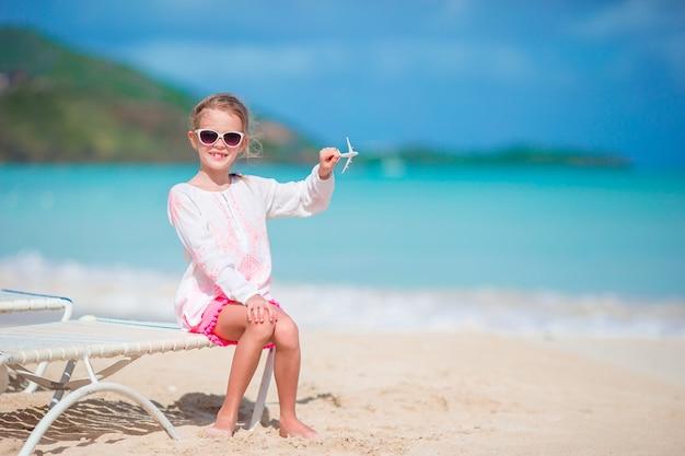 白い砂浜の手でおもちゃの飛行機との幸せな女の子。