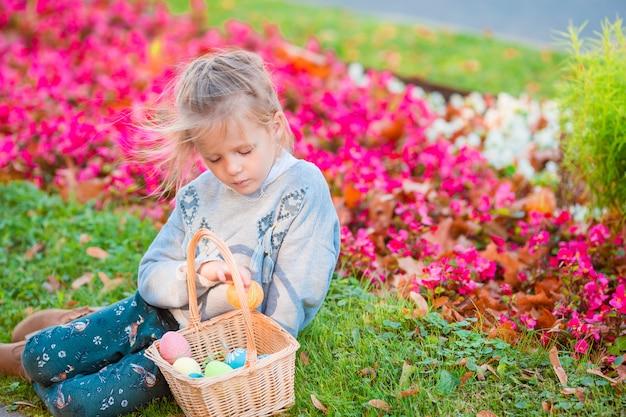 春の日の屋外でイースターエッグがいっぱい入ったかごとバニーの耳を着て小さな子供