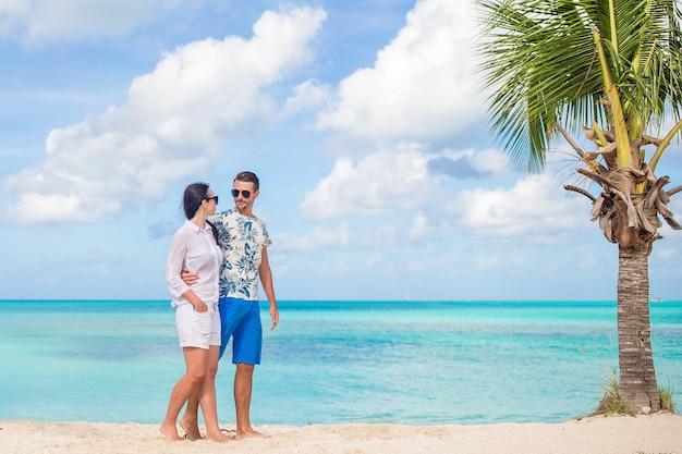 ビーチの上を歩くと夏休みを楽しんでいる素敵なカップル