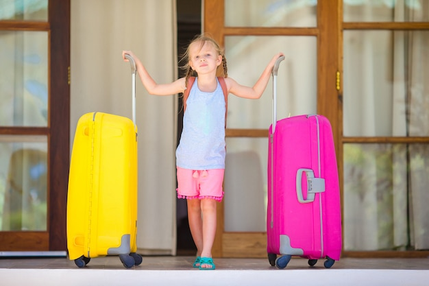 Очаровательная маленькая девочка с багажом, готовым к путешествию