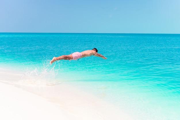 ターコイズブルーの海に飛び込む若い男