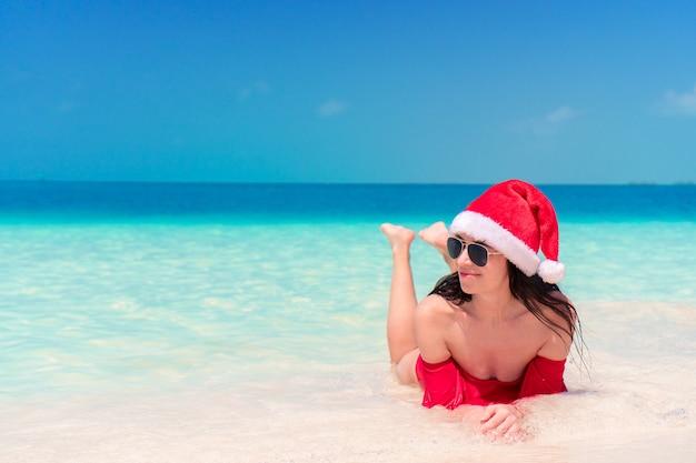 Молодая счастливая женщина в шляпе санта в купальнике на белом пляже на рождественские праздники