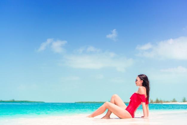 帽子と熱帯のビーチで若い女性