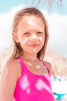 父は娘の鼻に日焼け止めを塗ります。