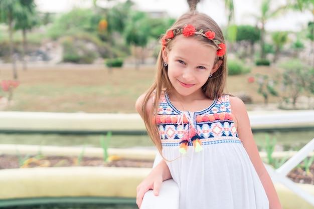 カリブ海の白い砂浜に沿って歩く愛らしい少女
