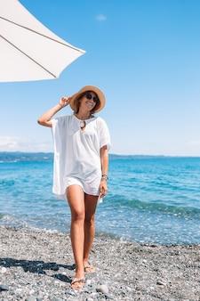 サンベッドの上に座って白いビーチでカクテルグラスと水着の若い女性