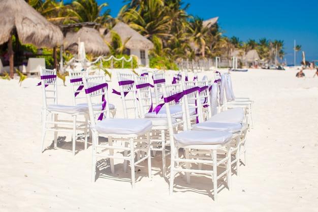 Белые свадебные стулья украшены фиолетовыми бантами на песчаном пляже