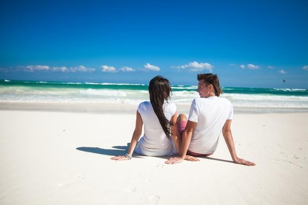 熱帯白いビーチに座って愛の若いカップルの背面図