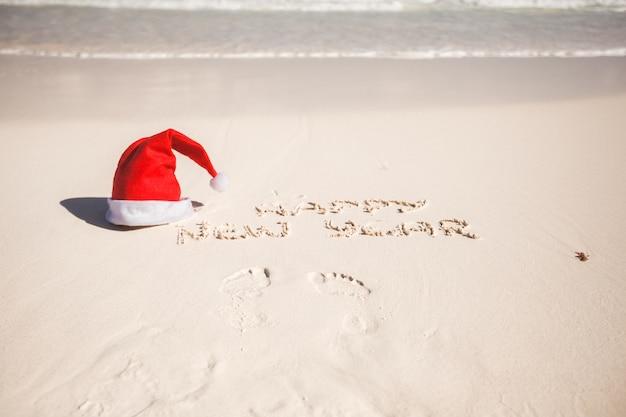 С новым годом написано в песке и санта шапке на белом песчаном пляже