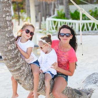 Счастливая кавказская семья наслаждаясь временем совместно на белом пляже