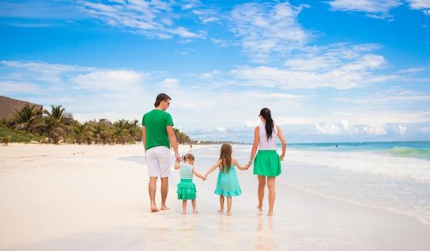 Вид сзади молодой семьи, глядя на море в мексике, пляж
