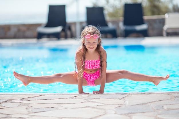 屋外スイミングプールの小さな幸せな女の子は彼女の休暇を楽しむ