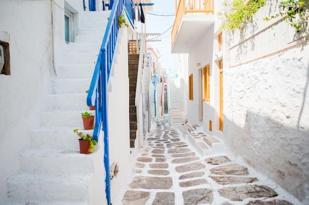 Узкие улочки острова с синими балконами, лестницами и цветами.